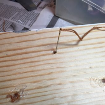 Needle inserted into bottom of Barbie wooden bed to attach Barbie doll bed mattress to the bed.