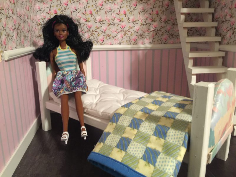 Barbie sitting on her new Barbie doll bed DIY mattress for her wooden bed.