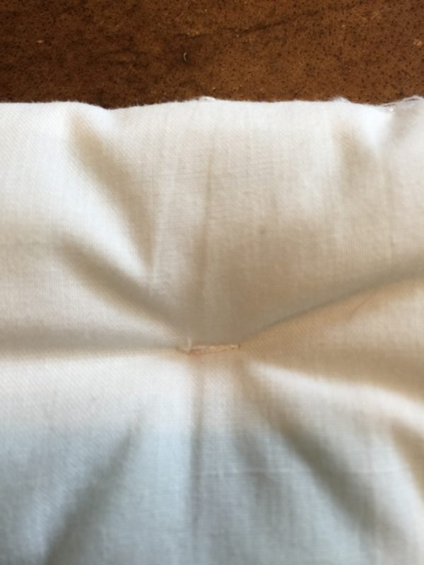 Close-up of tucks for Barbie doll bed DIY mattress for wooden bed.
